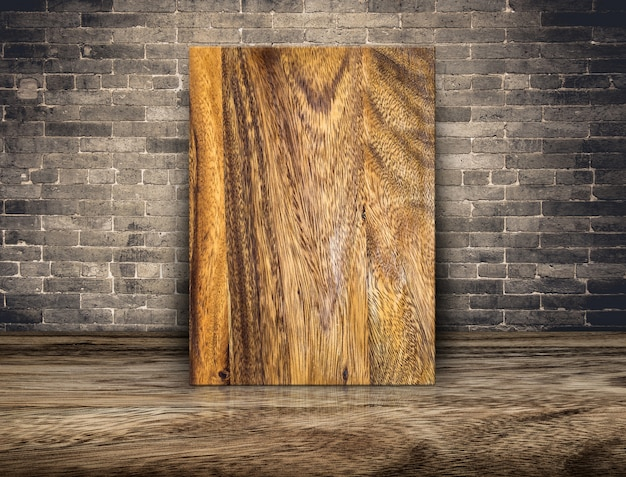 Blank plank wood board at grunge brick wall and wood floor