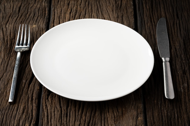 Blank plate with fork and spoon on wood