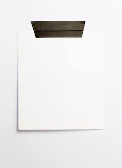 Blank polaroid photo frame with soft shadows and black scotch tape isolated on white paper background