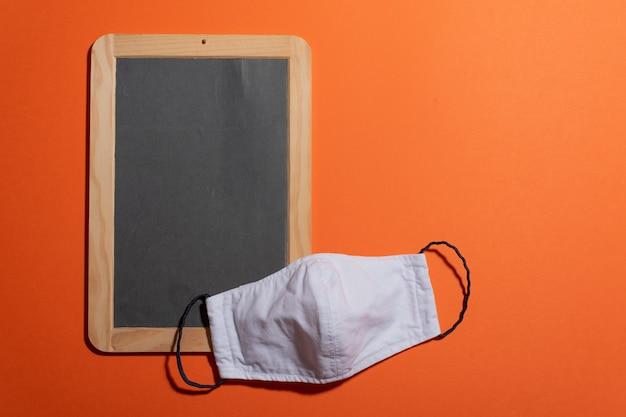 空白のポータブル黒板、diyフェイスマスク、暖かいカラーコピースペース