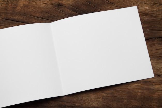 빈 세로 모형 종이입니다. 갈색 나무 테이블에 고립 된 브로셔 잡지