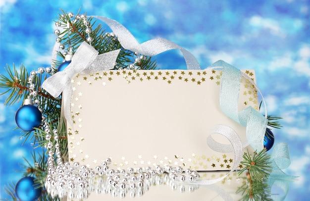 파란색 배경에 빈 엽서, 크리스마스 공 및 전나무 나무