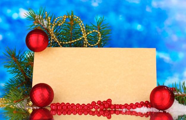 Пустая открытка, новогодние шары и елка на синем фоне