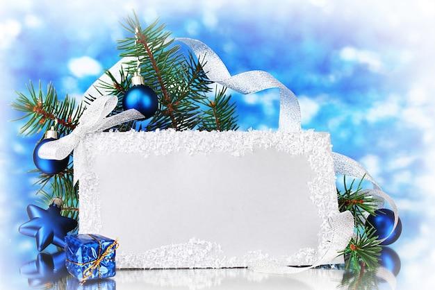 Пустая открытка, новогодние шары и елка на синей поверхности