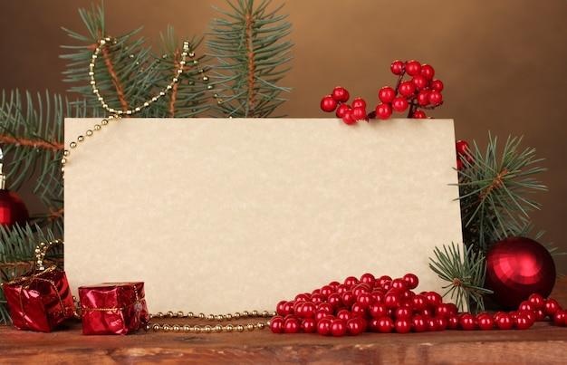空白のはがき、クリスマスボール、茶色の背景の木製テーブルの上のモミの木