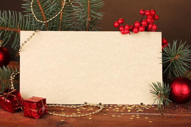 갈색 배경에 나무 테이블에 빈 엽서, 크리스마스 공 및 전나무 나무