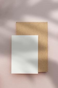 Cartolina in bianco con busta su una rosa