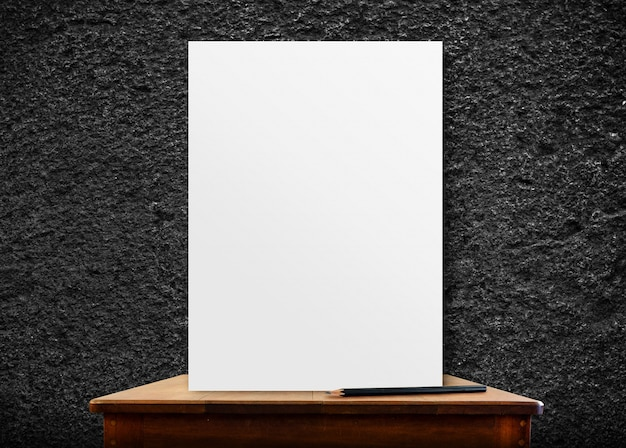 Blank poster frame on wood table at black stone wall,perspective background