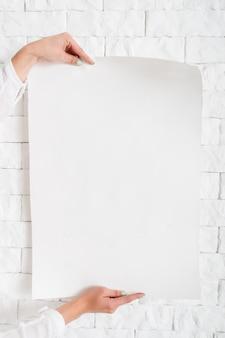 壁に対して女性の手で空白のポスター
