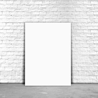 흰색 벽돌 벽 옆에 빈 포스터 종이 서