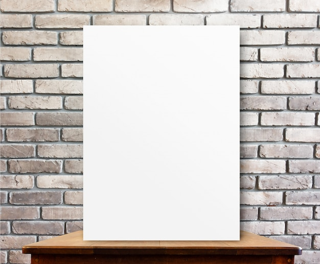 Blank poster on wood table at brick wall,perspective background