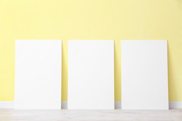 Пустые плакаты возле цветной поверхности
