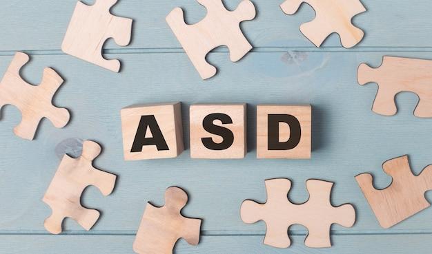 テキストasd自閉症スペクトラム障害の空白のパズルと木製の立方体は水色の背景にあります。