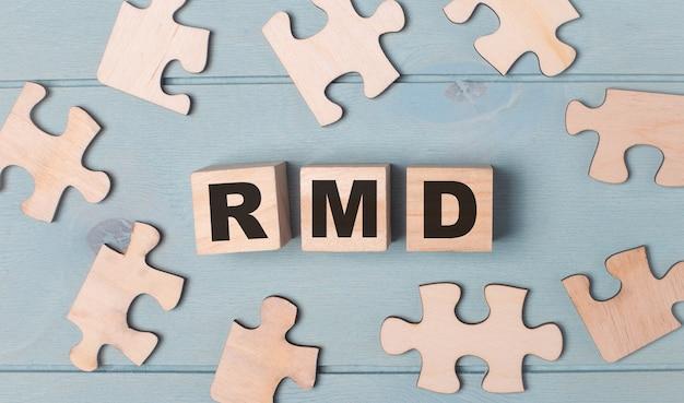 Пустые пазлы и деревянные кубики с текстом «минимальные раздачи rmd» лежат на голубом фоне.