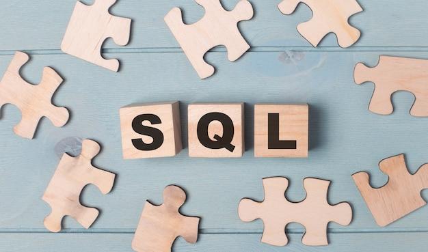 Пустые головоломки и деревянные кубики с текстом sql structured query language лежат на голубом фоне. Premium Фотографии
