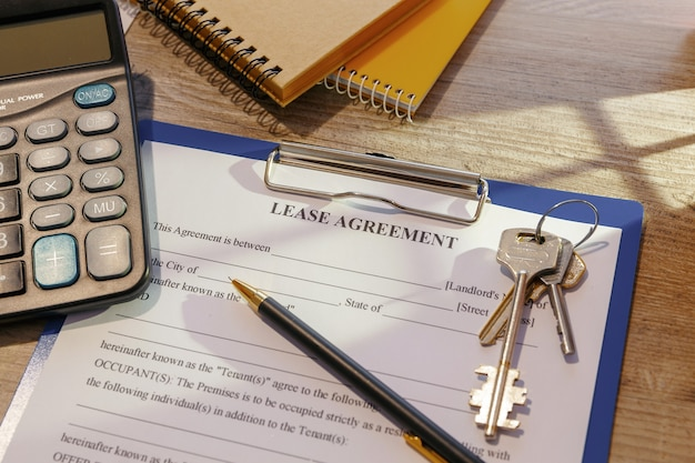 Blank real estate lease agreement, keys and calculator on office desk