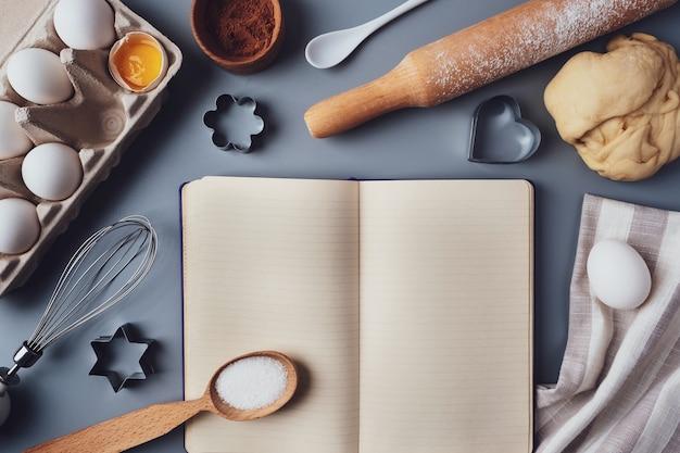 텍스트, 롤링 핀, 곰팡이, 계란, 반죽, 설탕, 평평한 평지, 보기, 복사 공간을 위한 빈 요리법 책. 회색 배경에 베이킹 재료와 주방 용품. 휴가를 위한 쿠키.