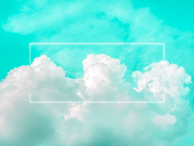 美しい緑のネオンの空を背景に、夢のようなふわふわの雲に空白の長方形の白い輝くライト フレーム。コピー スペースを持つ抽象的な最小限の自然で豪華な背景。