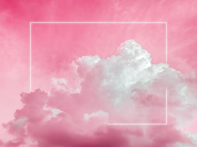 美しい赤いネオンの空を背景に、夢のようなふわふわの雲に空白の長方形の白い輝くライト フレーム。コピー スペースを持つ抽象的な最小限の自然で豪華な背景。