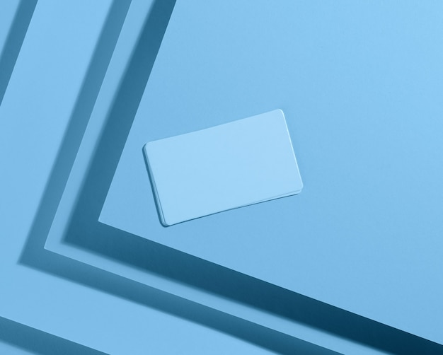 Blank  rectangular business card on creative blue background from sheets of paper with shadow, top view