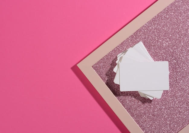 Blank rectangular business card lies on a modern pink background sheets of paper with a shadow. business template, flat lay