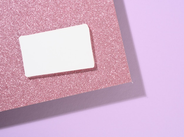 Blank rectangular business card lies on a modern purple background sheets of paper with a shadow