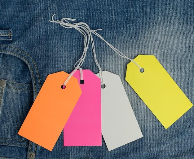 Пустые прямоугольные картонные цветные бирки на фоне синих джинсов, вид сверху