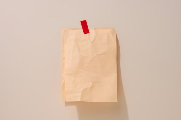 明るいベージュの背景に接着された空白の長方形のしわくちゃのベージュの紙。碑文、発表のための場所