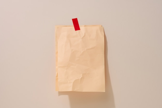 Blank rectangular crumpled beige sheet of paper glued on a light beige background. place for an inscription, announcement