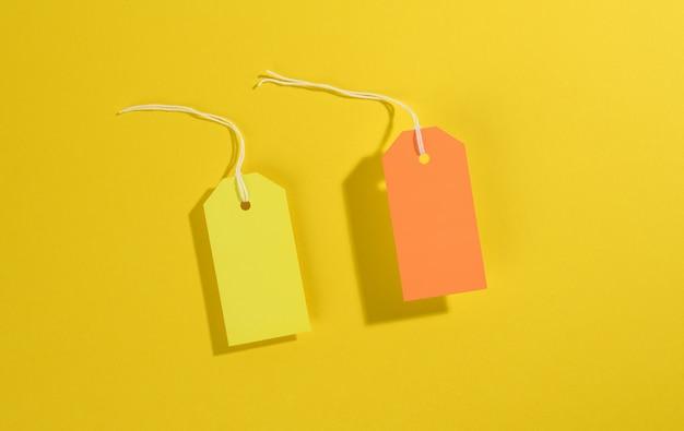 Пустые прямоугольные бумажные желтые и оранжевые ценники с белой веревкой на желтом фоне, вид сверху
