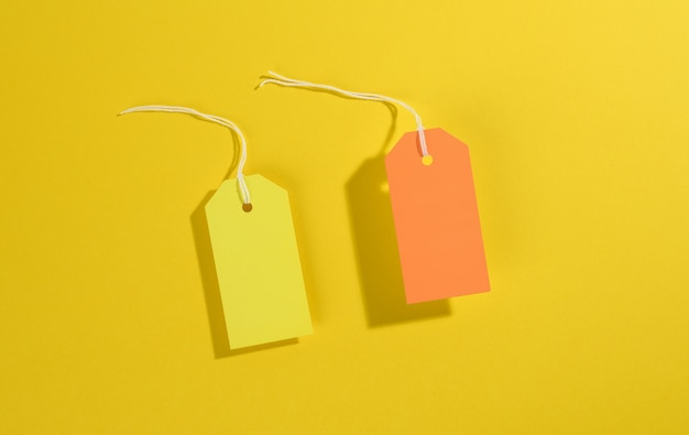 Blank rectangular paper yellow and orange price tags with white rope on yellow background, top view
