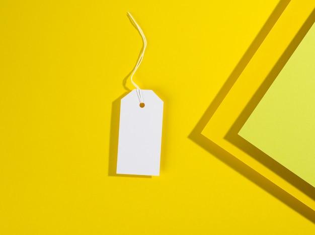 Пустой прямоугольный бумажный желтый ценник с белой веревкой на желтом фоне, плоская планировка