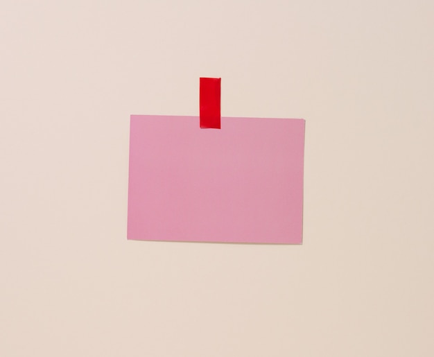 Blank rectangular pink sheet of paper glued on a light blue background. place for an inscription, announcement