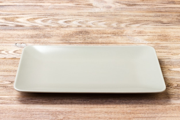Blank rectangular plate on wooden background. top view