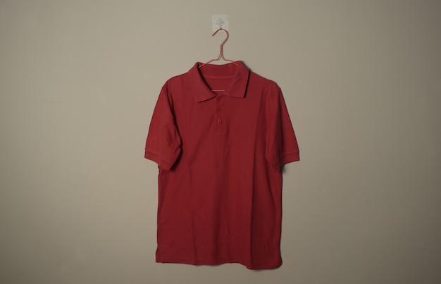 壁の背景の正面側面図でハンガーに空白の赤いカジュアルなtシャツのモックアップ