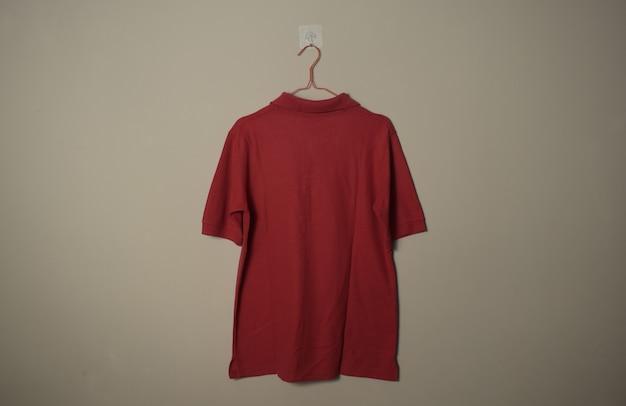 壁の背景の背面図でハンガーに空白の赤いカジュアルなtシャツのモックアップ