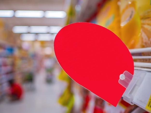 Пустой красный дисконтный ярлык на полках продуктов в супермаркете