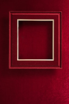 Пустая красная фетровая фоторамка на бархатной красной фетровой ткани сверху