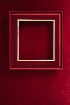 Blank red felt photo frame on velvet red felt fabric  top view