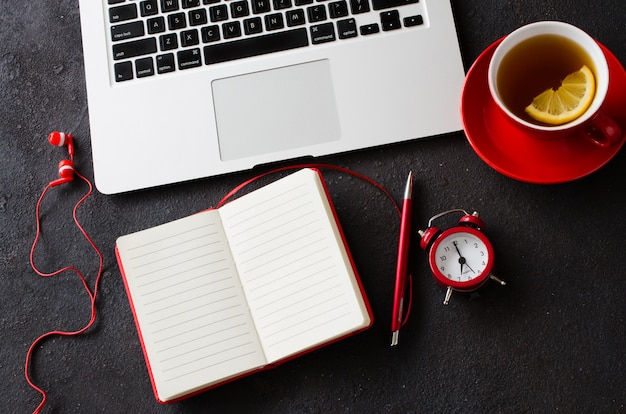 Blank red notebook, computer laptop, alarm clock, headphones and cup of tea