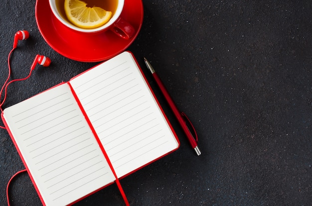 Blank red notebook, computer laptop, headphones and cup of tea.