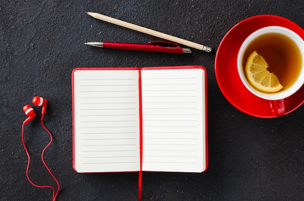 Blank red notebook, computer laptop, headphones and cup of tea