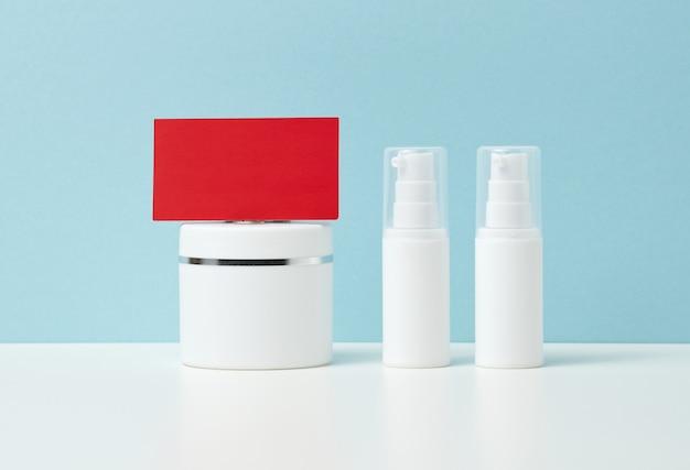 空白の赤い紙の名刺と青い背景の化粧品用のプラスチックの白い容器のセット。ブランドコンセプト、プロモーション、製品デモンストレーション