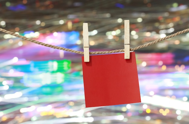 Blank red paper notes hanging on clothesline.