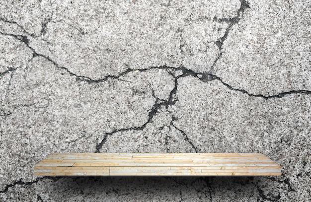 Blank rock stone display shelf on crack cement wall