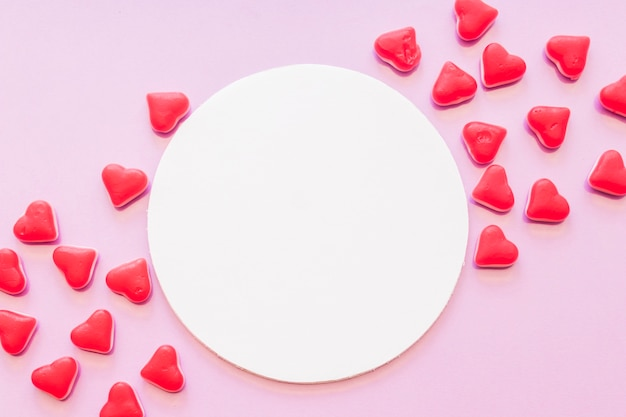 Blank round frame decorated with red heart shape candies on pink background