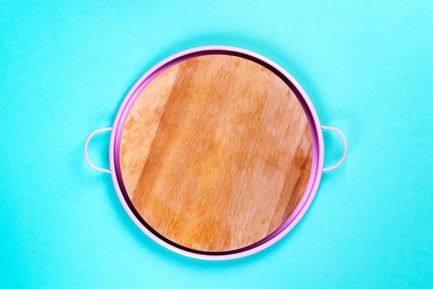 明るい青色の背景にピンクのパンで空白の丸い木の板。平干し。