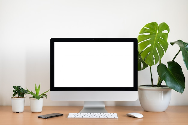 Blank screen of all in one computer, keyboard, mouse, monstera plant pot and small plant pots  on wooden table