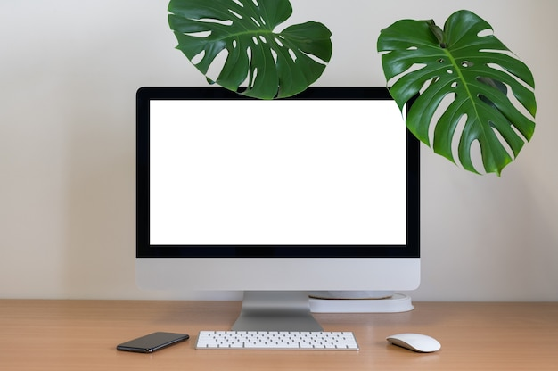 Blank screen of all in one computer with monstera and smartphone on table