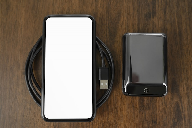 Blank screen of black smartphone and portable battery charger on the wood table.
